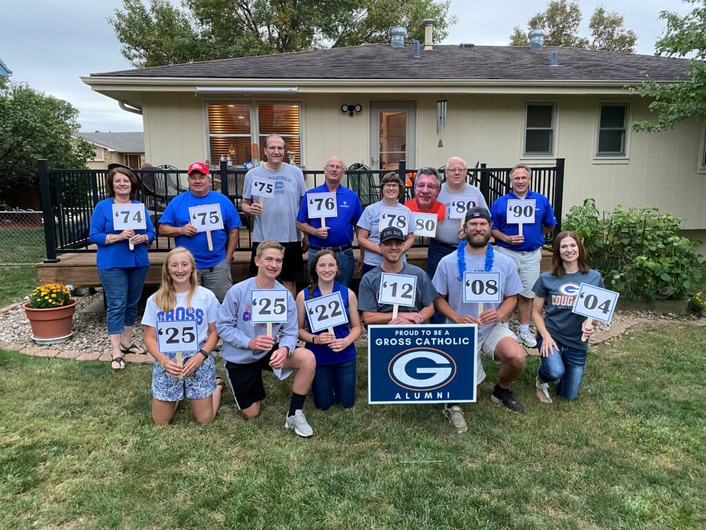 Group of Gross Catholic Alumni pose with signs