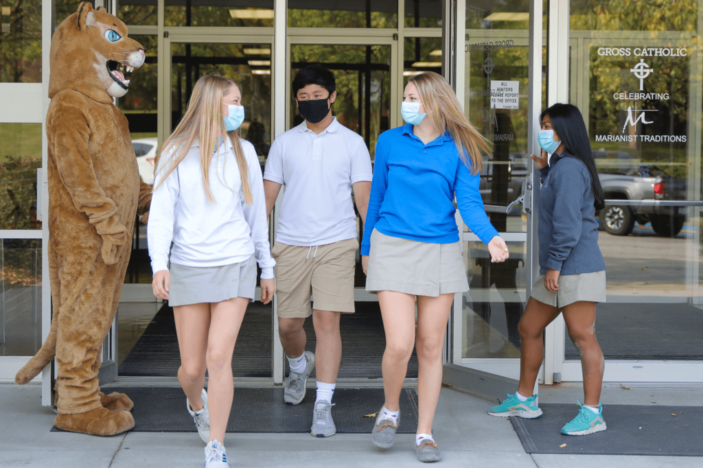 Freddie Cougar mascot holds the door for female students as they exit the school